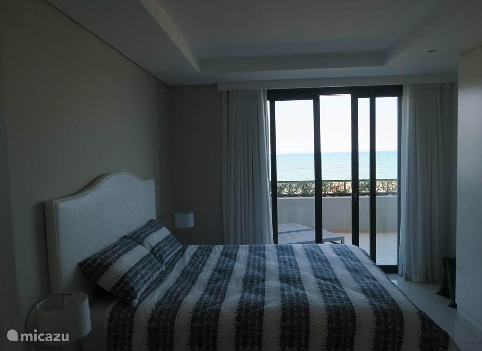 hoofdslaapkamer met uitzicht op terras en zee.