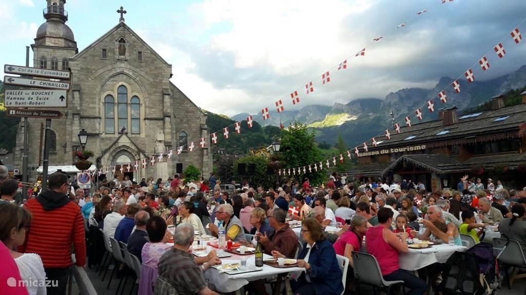 Nationale feestdag van Frankrijk, 14 juli, gezamenlijk eten op het plein voor de kerk met op de achtergrond de bergketen van de Aravis