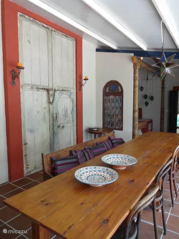 In het ruime huis staat een robuuste tafel waaraan heerlijk kan worden gegeten. De oude deuren en oosterse details maken het huis tot een orientaal paradijsje.