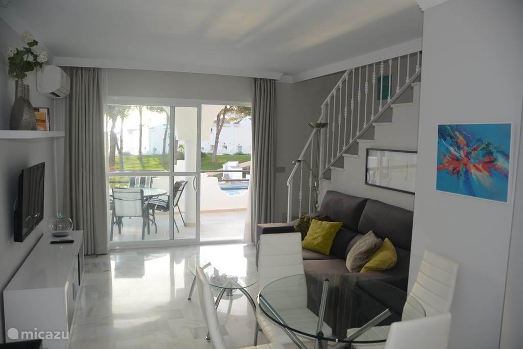 De woonkamer met veel licht inval heeft direct toegang tot 1 van de 3 terrassen doormiddel van een grote schuif deur.