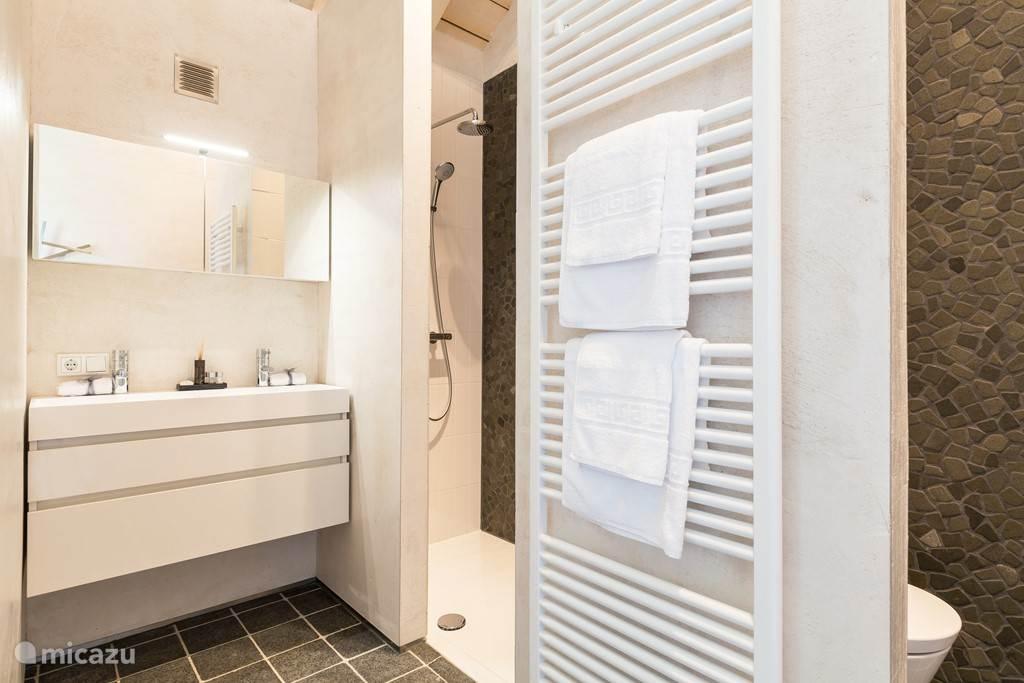 De moderne badkamer, met een luxe badkamermeubel, handdoekradiator en inloopdouche met regendouchekop.