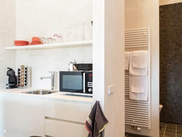 Close-up van een kitchenette, voorzien van apparatuur (koelkast, koffiemachine, waterkoker, combi-magnetron, flexibele kookplaten, service en bestek).