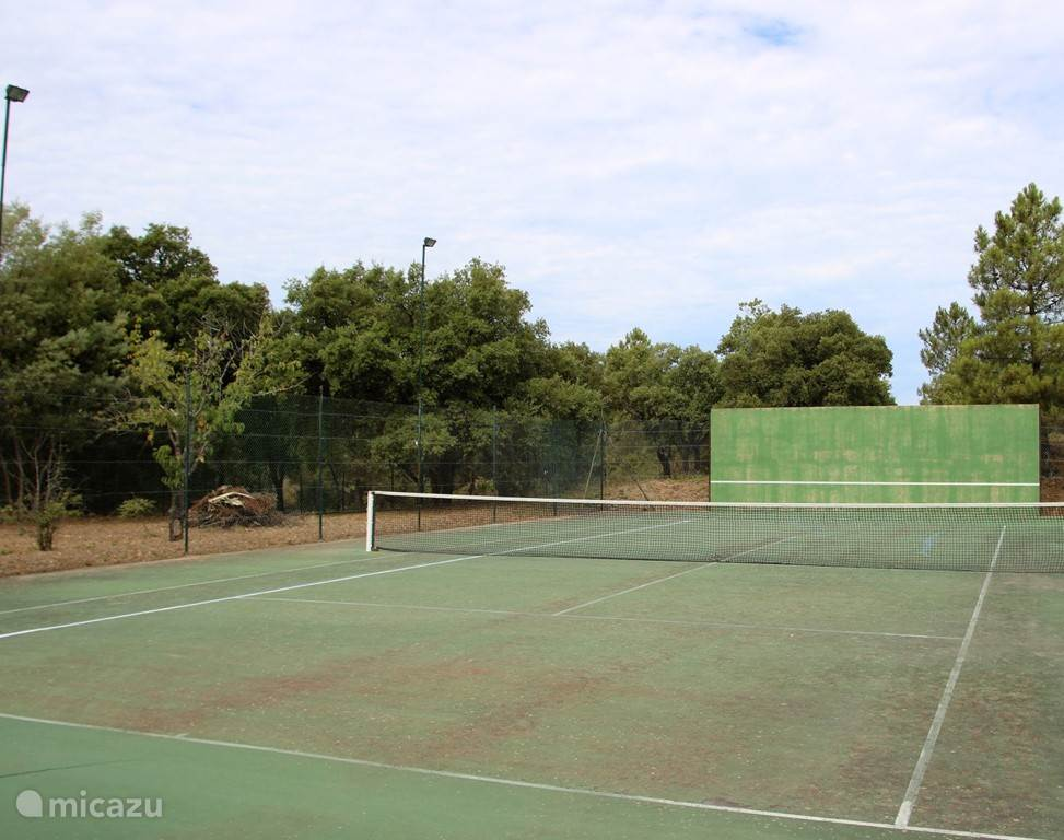 Private tennis court with squash wall