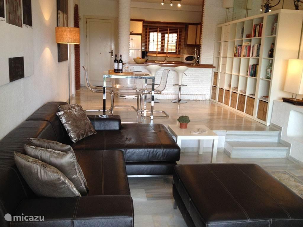 Woonkamer appartement Tobago met loungebank en eethoek