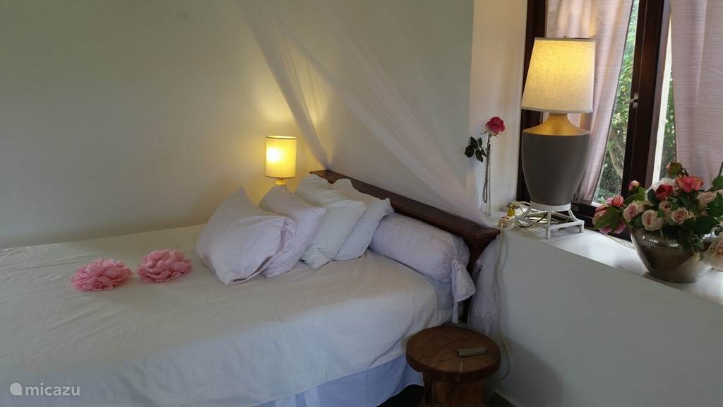 Het bed voorzien van een extra mosquito net voor de regentijd.