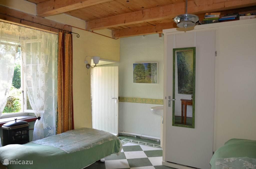 De groene slaapkamer, met deur naar buiten, eigen douche/wc op de kamer.