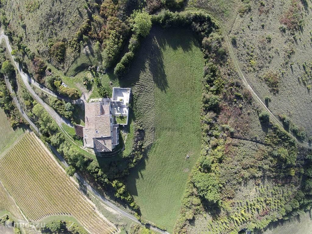 De boerderij vanuit de lucht, gelegen midden in de natuur.