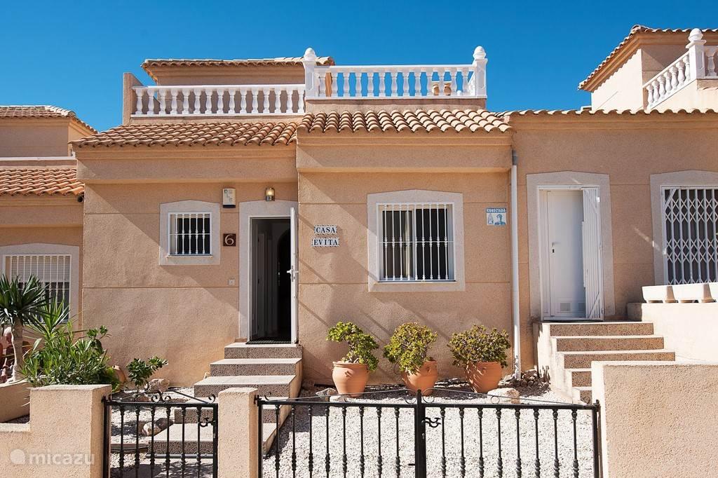 Het huis is een split level huis. Aan de straatzijde ziet u van links naar rechts: het raam van badkamer 1, de voordeur, het raam van slaapkamer 1, de deur van de schuur. Aan de bovenzijde is het solarium zichtbaar. De voordeur is goed bereikbaar via een langzaam stijgende trap met brede treden.