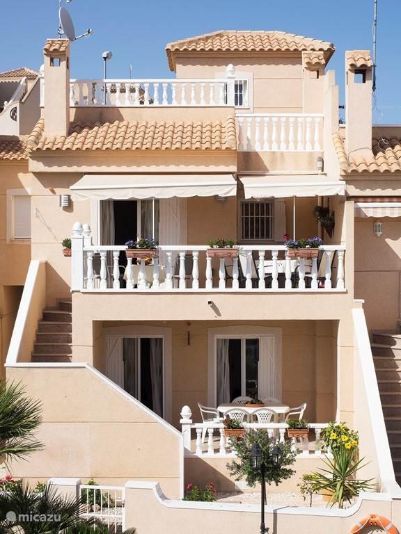 Aan de tuinzijde zijn de 3 verdiepingen zichtbaar. Van boven naar beneden: de reling van het solarium (dakterras), het terras van de woonkamer, de porch. Via de tuinzijde heeft u direct toegang tot een grote gezamenlijke tuin met zwembad.
