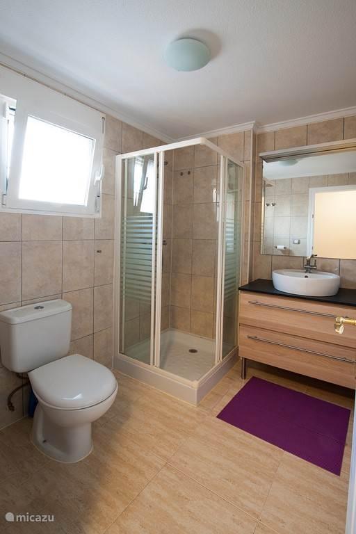 Badkamer 1 bevindt zich direct aan de hal en tegenover slaapkamer 1. Deze badkamer bevat: douche, toilet, vaste wastafel met meubel, aparte kast (niet op foto zichtbaar), föhn.