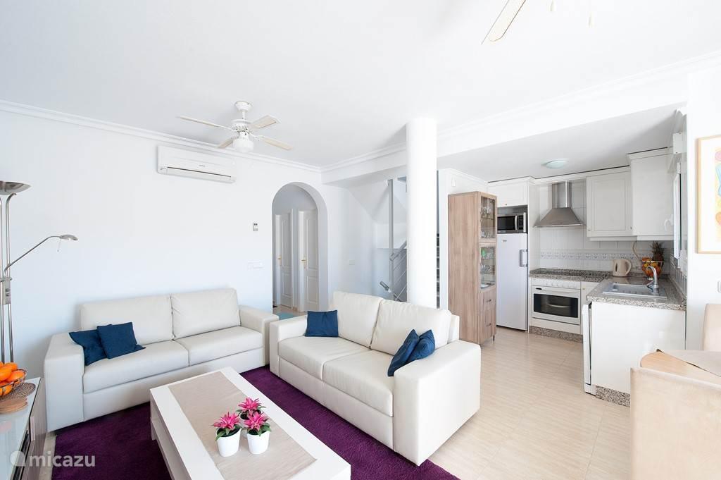 De woonkamer is direct verbonden met een open keuken en vanuit de hal bereikbaar. Aan deze hal bevinden zich slaapkamer 1, badkamer 1 en een apart washok met wasmachine. De eettafel is geschikt voor 6 personen.