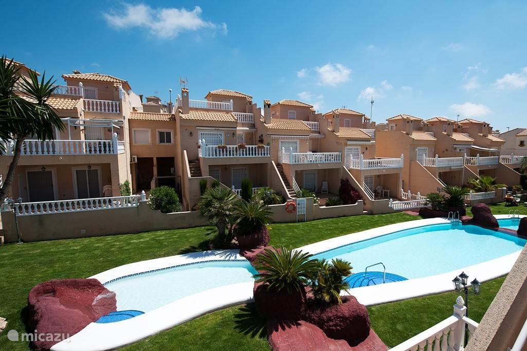 De achterzijde van Casa Evita met de gemeenschappelijke tuin plus zwembad.