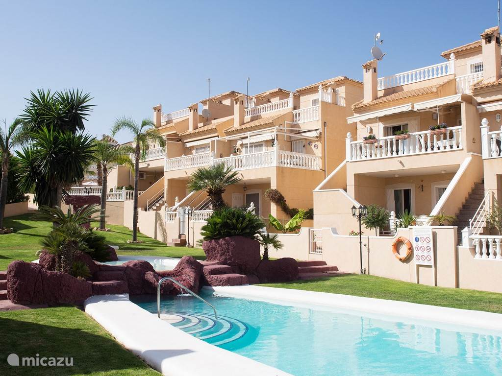Aan de tuinzijde zijn de 3 verdiepingen zichtbaar. Via de tuinzijde heeft u direct toegang tot een grote gezamenlijke tuin met zwembad. Op deze foto ziet u het hekje tussen huis en gezamenlijke tuin met zwembad. Dit hekje is afsluitbaar.