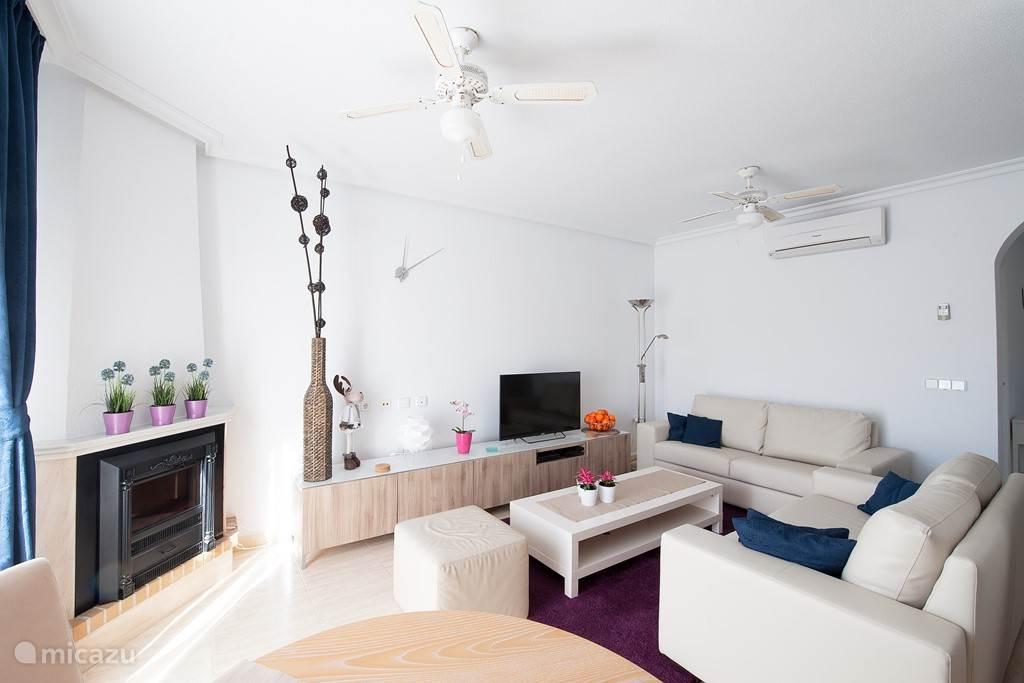 Op de begane grond bevind zich een grote woonkamer met zithoek en eethoek. Voorzien van een grote TV met Nederlandse en buitenlandse zenders. Wifi is gratis beschikbaar. De woonkamer is voorzien van een airco die zowel kan koelen als verwarmen. Bovendien is er een elektrische open haard.