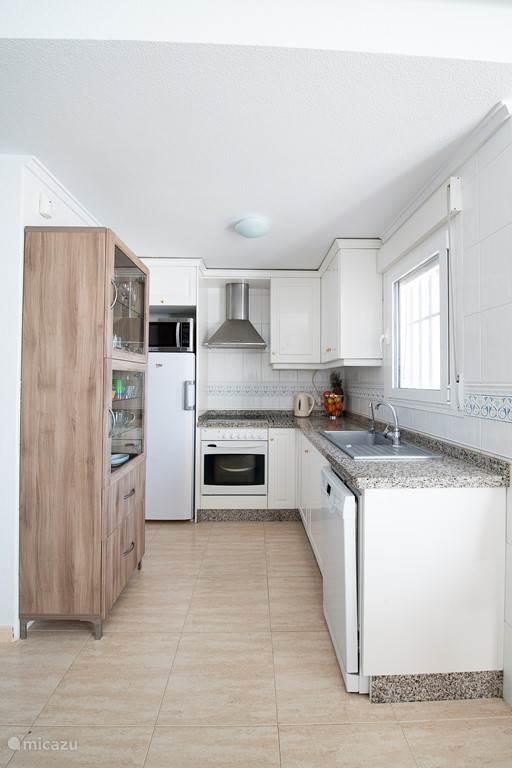 De open keuken kijkt uit op het terras van de woonkamer. In de keuken zijn aanwezig: grote koelkast, magnetron, oven, 4 keramische kookplaten, afzuigkap, waterkoker, koffiezetapparaat, staafmixer, citruspers, broodrooster, stomer, voldoende pannen en potten, vaatwasser (vanaf april 2016).