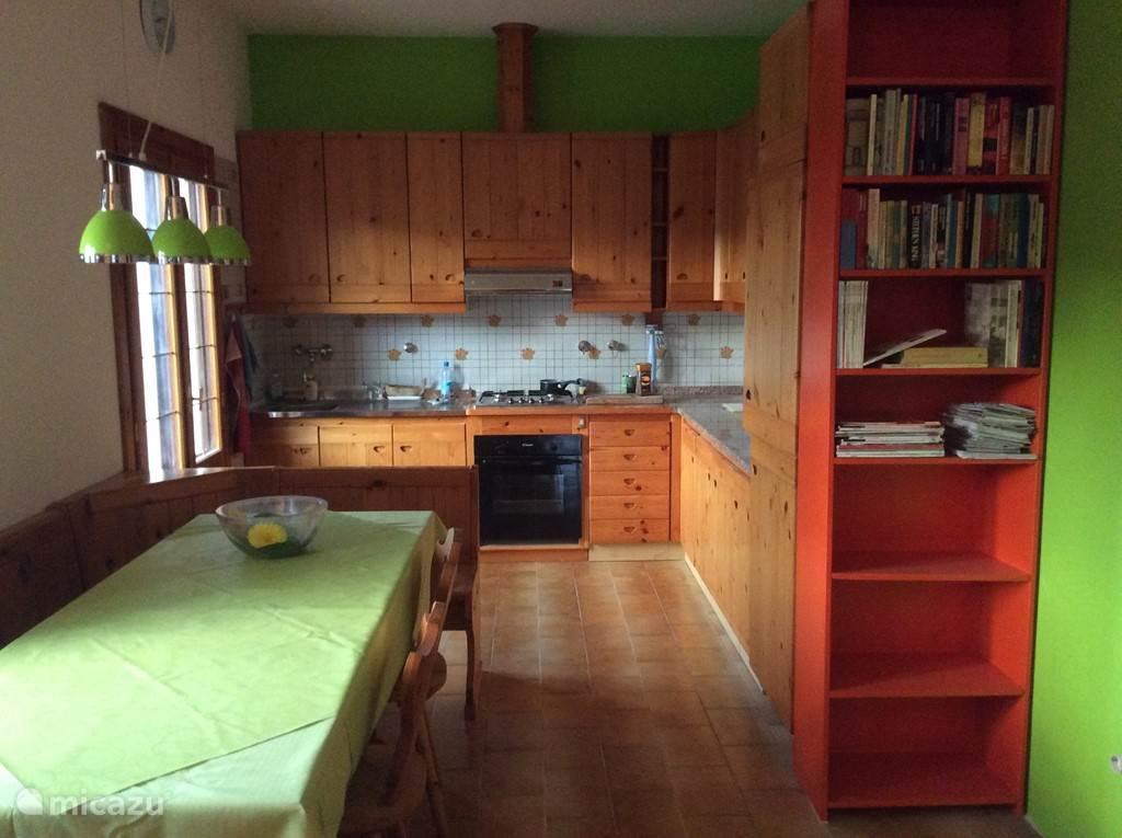 De gezellige woonkeuken met deuren naar het terras