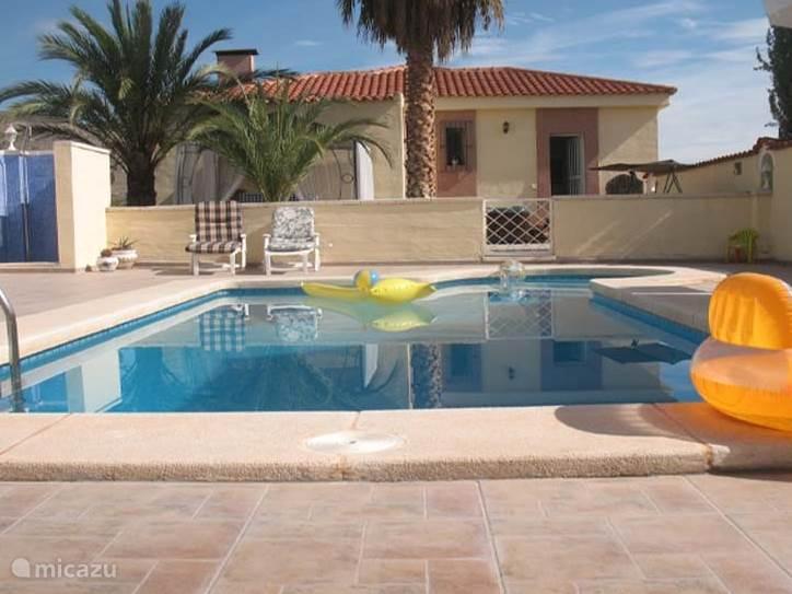 zwembad met buitendouche en zicht op het huis