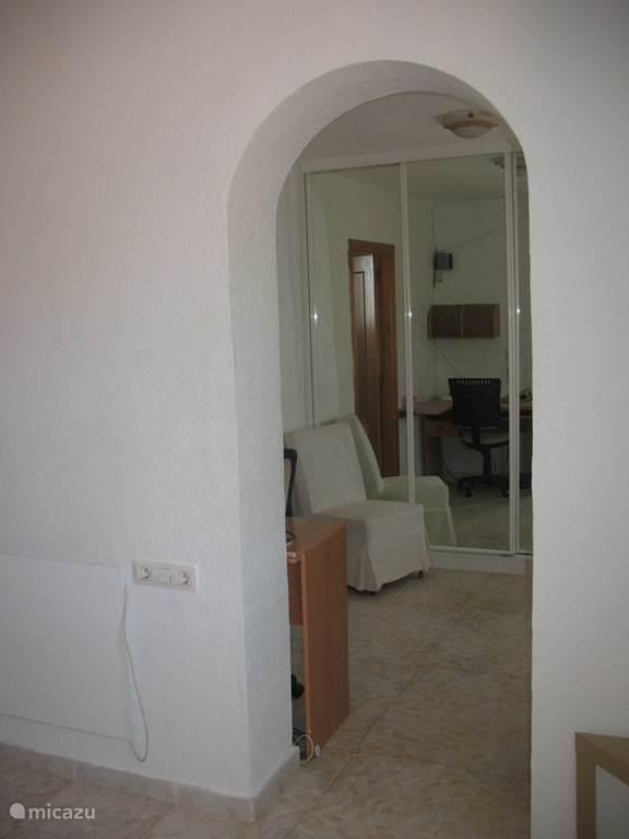 van de slaapkamer via een tussenruimte. met een spiegel wandkast over de gehele breedte, hier staat een baby bed. naar de badkamer
