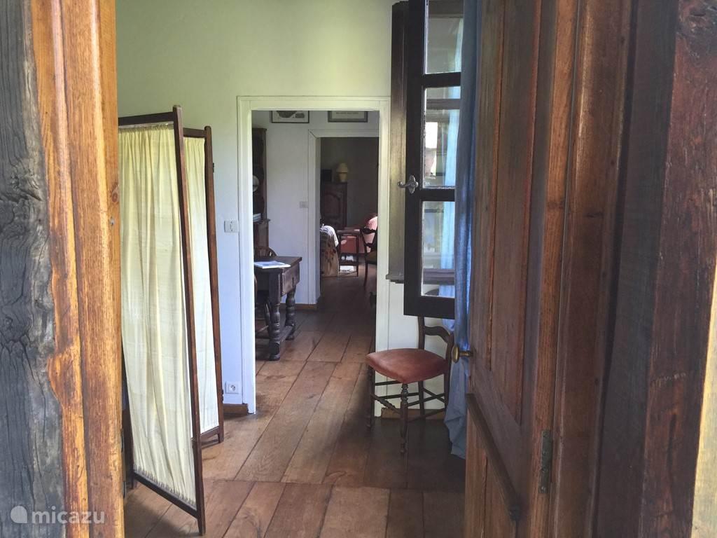 Doorkijkje op de woonverdieping. De kamers liggen in elkaars verlengde. De foto is genomen vanaf de veranda. Achtereenvolgens zie je de slaapkamer, de eet-werkkamer en de woonkamer.