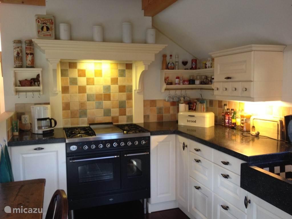 Keuken, het kookgedeelte is voorzien van een luxe gasfornuis met 2 gescheiden ovens. De gehele keuken is ingericht in de stijl van een boerderij.