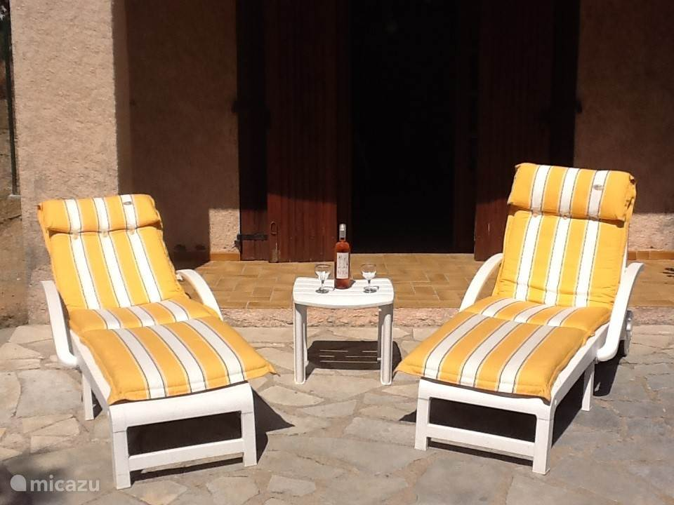 drie ligbedden voor een zonnebad in de tuin, achter het huis