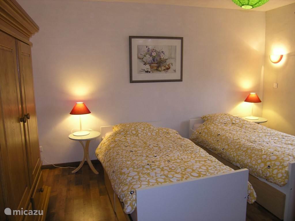 2 persoons slaapkamer met enkele bedden en kinderbed
