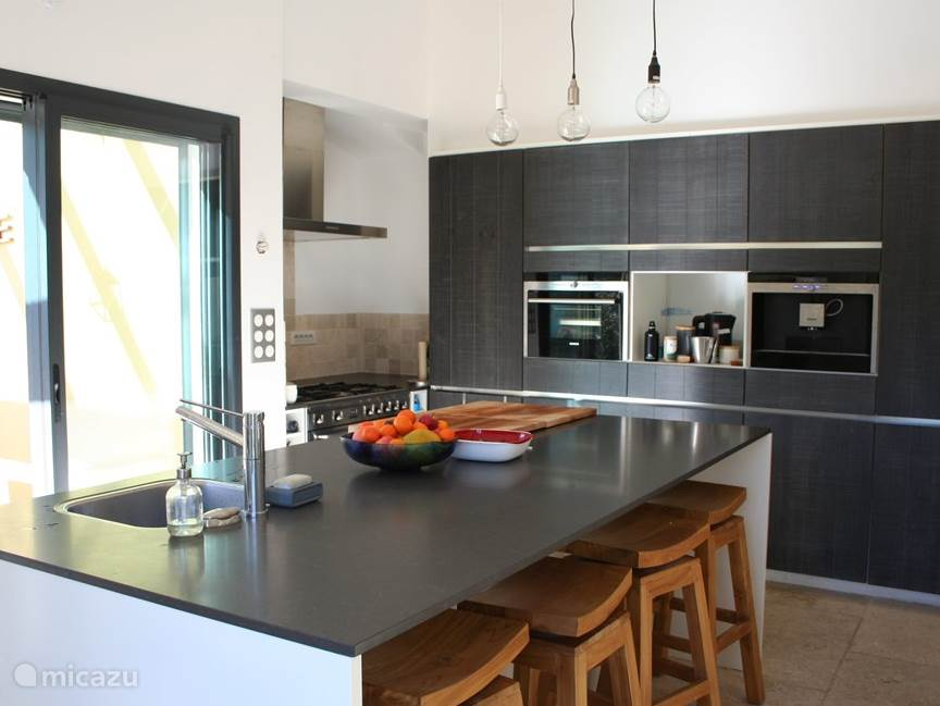 Nieuwe schitterende open keuken met spoeleiland en grote kastenwand, 6-pits gasfornuis met grote oven, stoomoven, koffiemachine en vaatwasmachine.