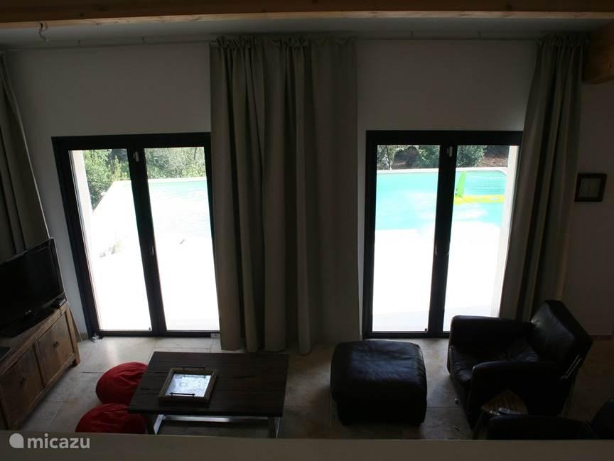 Mooie woonkamer met prachtig uitzicht over het zwembad en mediterrane tuin.