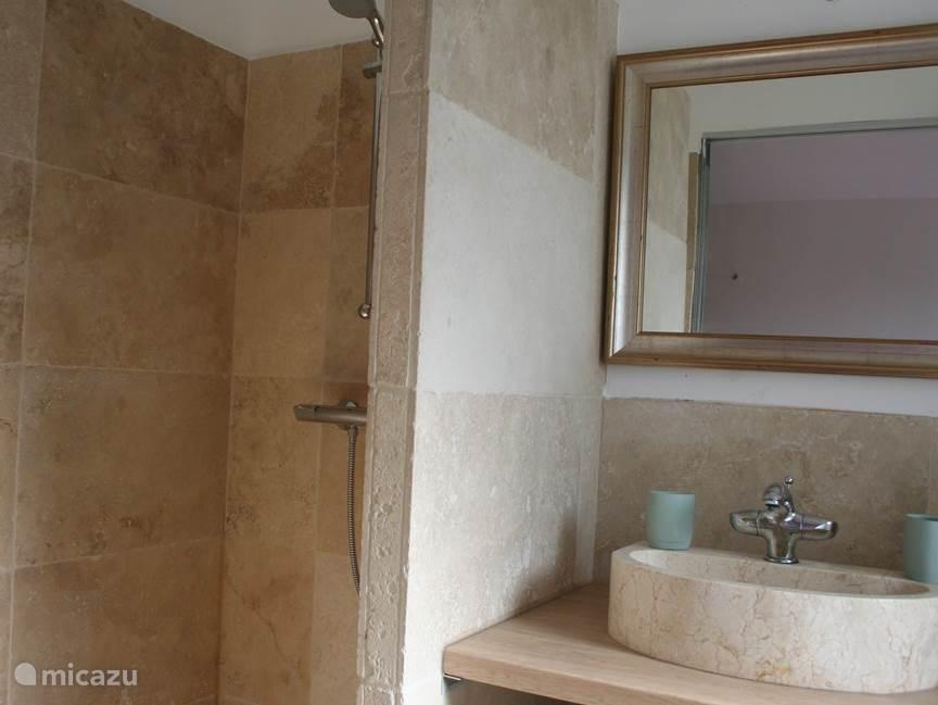 Mooie badkamer met marmeren vloer en wanden. Er is een mooie royale inloopdouche, wastafel en zwevend toilet.