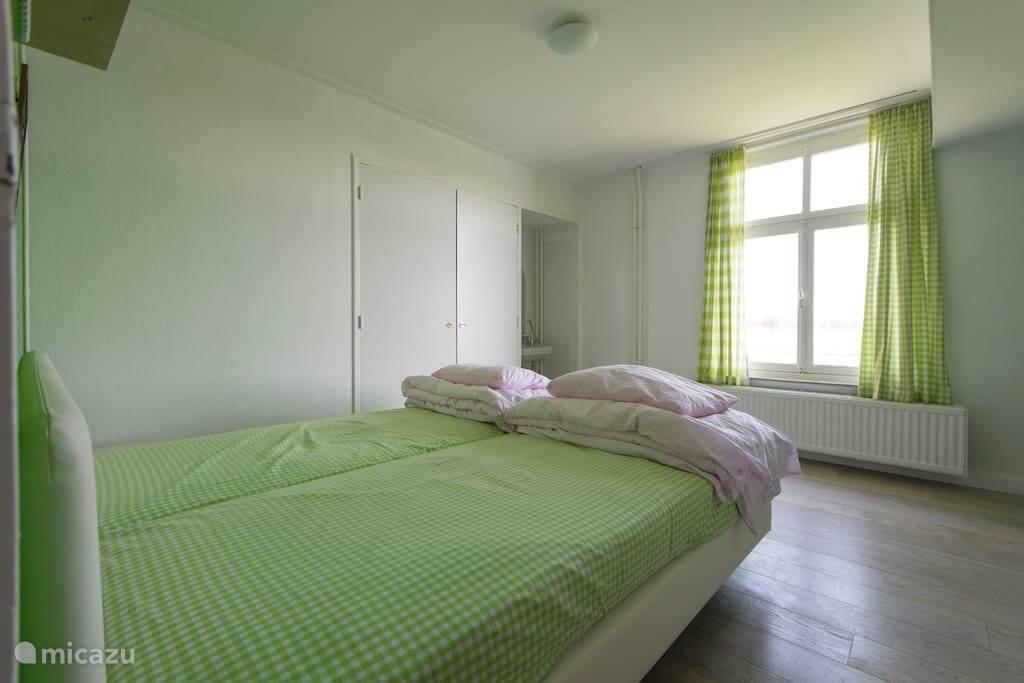 slaapkamer met kast  wastafel en uitzicht op de maas