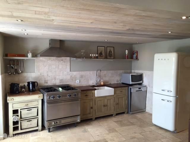 Keuken met afwasmachine, combi oven en koelkast met vriezer.
