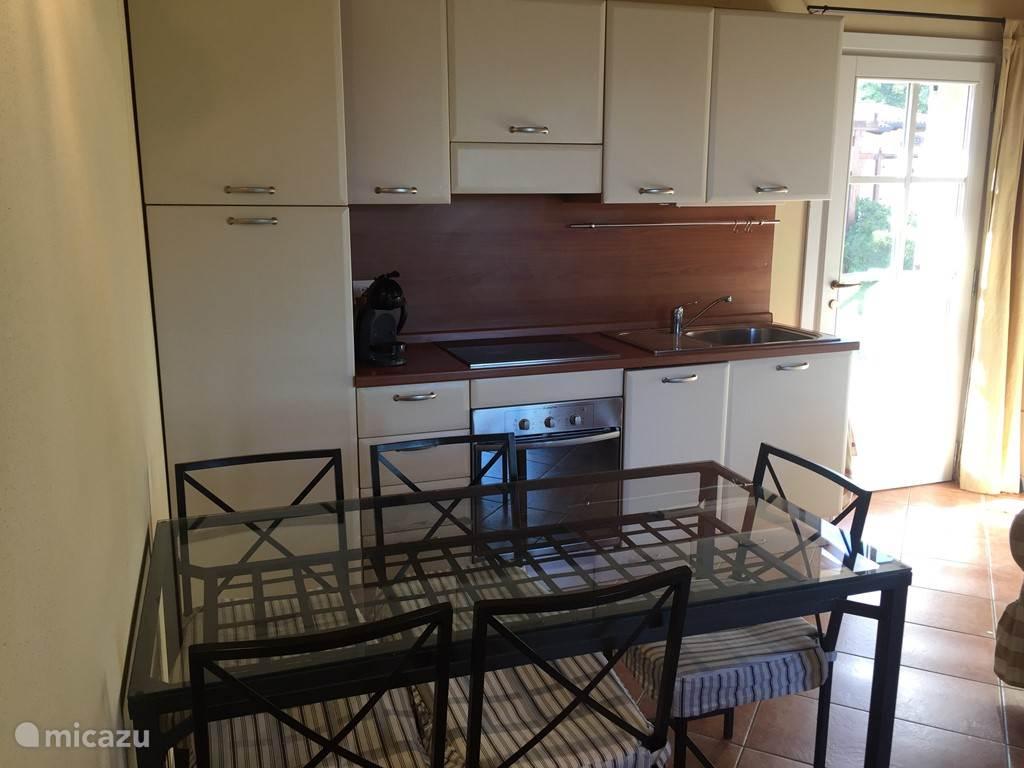 Open keuken, met afwasmachine, inductiekookplaat, oven, koelkast en vriezer. Met ruime eettafel en 5 stoelen.