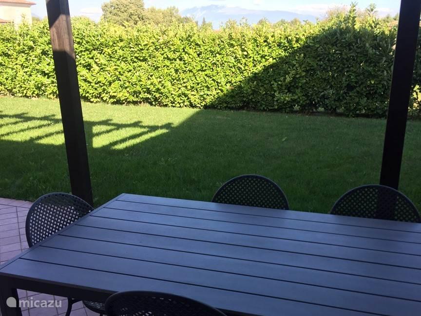 Achter-terras met tuin. Uitzicht op de bergen. s'Ochtend en middags zon. Terras-tafel met 5 terras-stoelen.