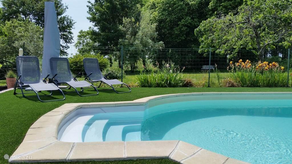 Zwembad met ligstoelen en parasols.
