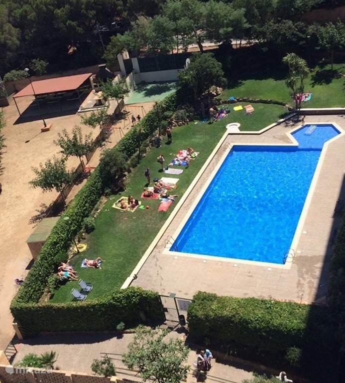 Zwembad met apart kinderbad gezien vanaf ons balkon. De zwembaden zijn omheind, u krijgt een sleutel van de poort. De afgesloten tuin naast het zwembad heeft een speeltuin, tafeltennistafels, meerdere BBQ's en een basketbalveld. Aan de andere kant van het appartement is de tennisbaan.