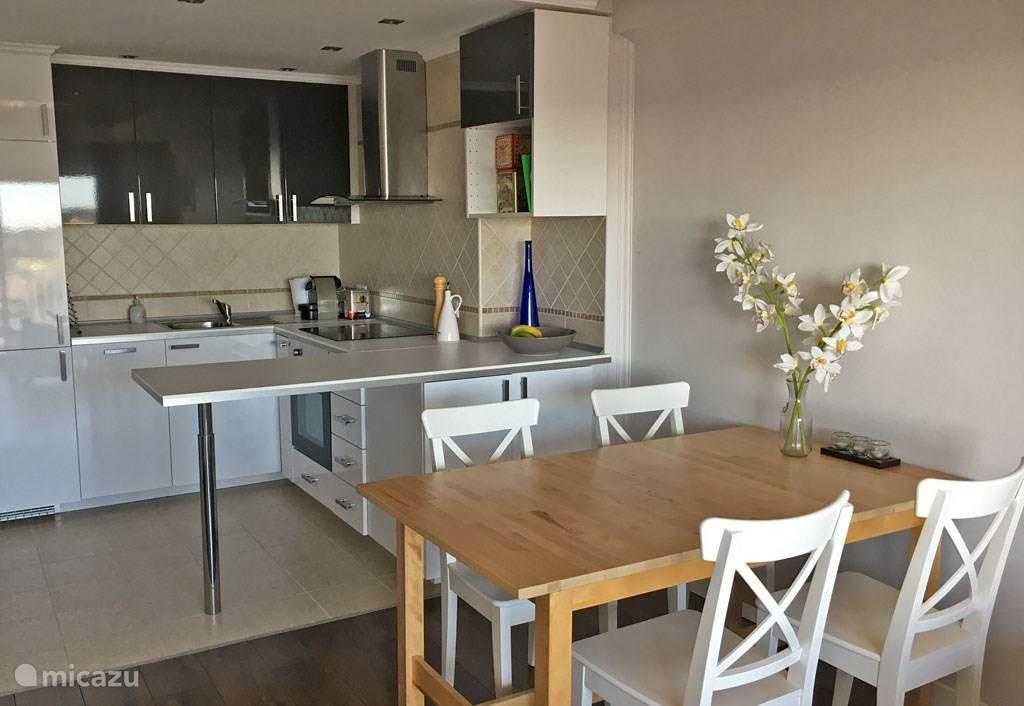 Huiskamer met eettafel en de open keuken met vaatwasser, koelkast, vriezer, kookplaat, oven en Nespresso koffieapparaat.