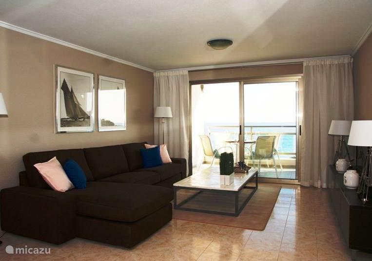 ruime woonkamer met aangrenzend terras met uitzicht op zee.