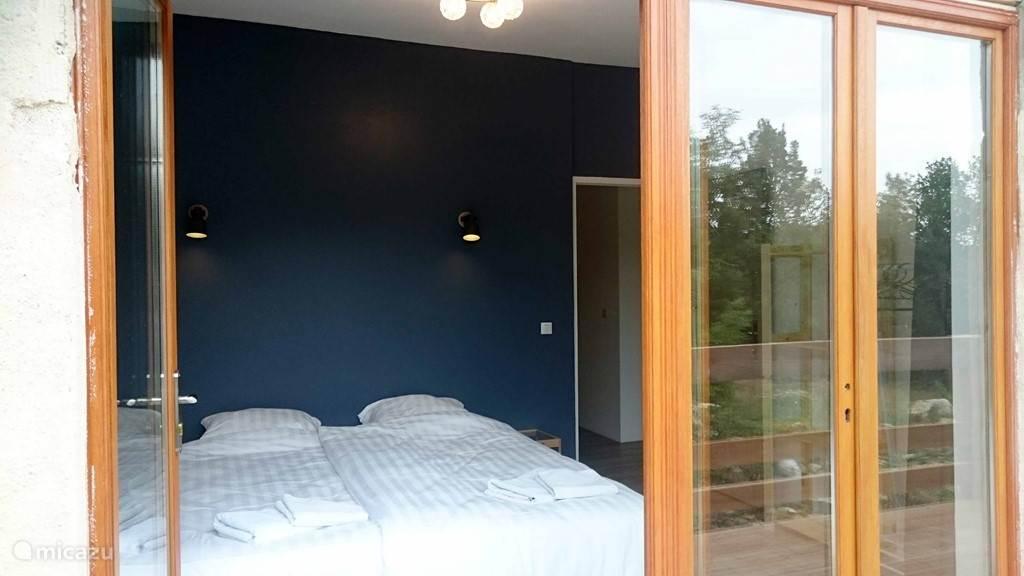 De master bedroom grenst aan het terras aan de achterkant en heeft heerlijke openslaande tuindeuren