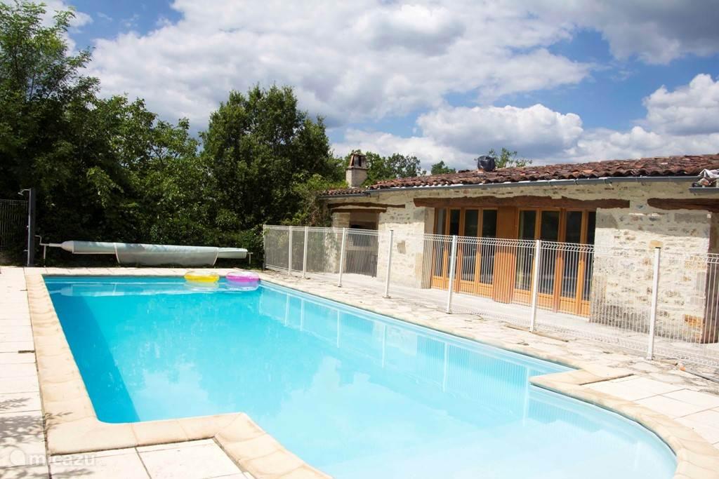 De gite Le Tournesol met openslaande tuindeuren ligt naast het zwembad.