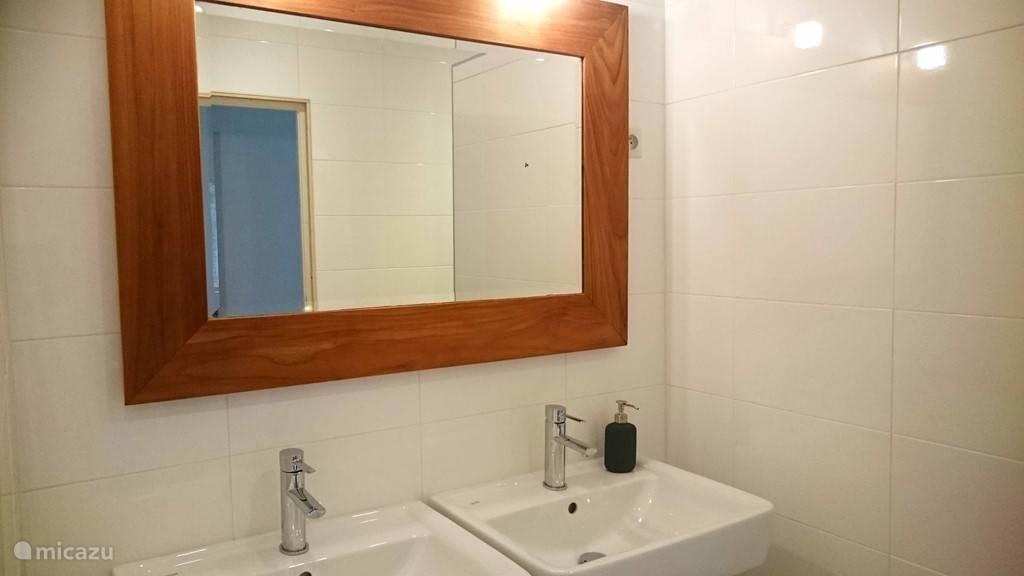 De badkamer heeft een dubbele wastafel
