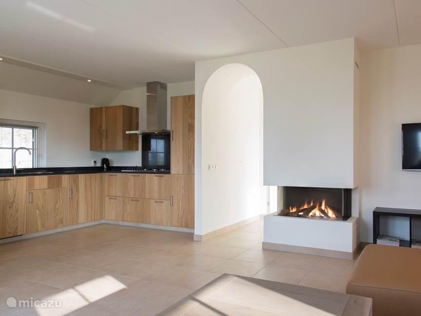 Luxe open keuken met kookplaat, vaatwasmachine, Illy espresso apparaat, combi-oven en koelkast met aparte vriezer