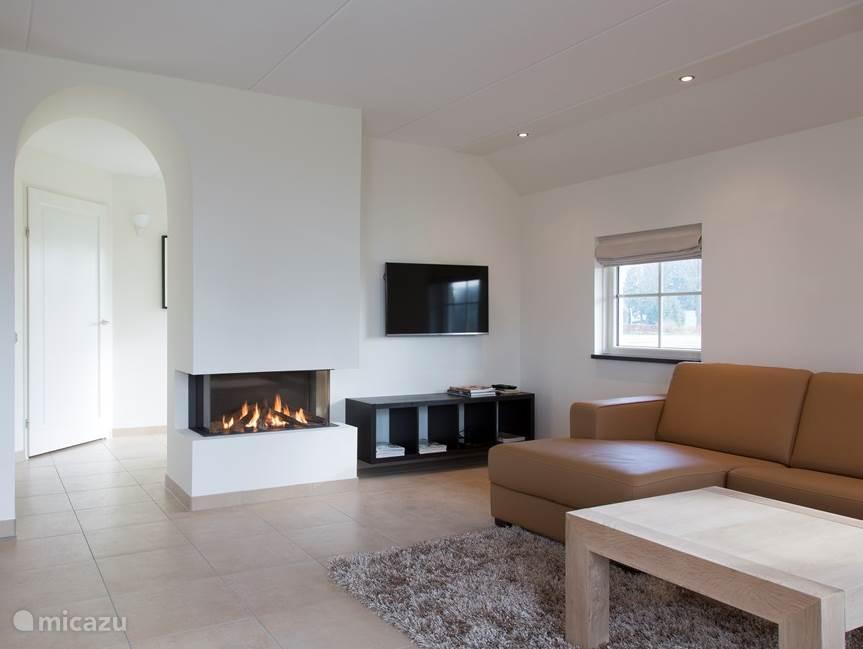 Ruime woonkamer met flatscreen tv, gasgestookte openhaard, vloerverwarming en openslaande deuren naar het terras.