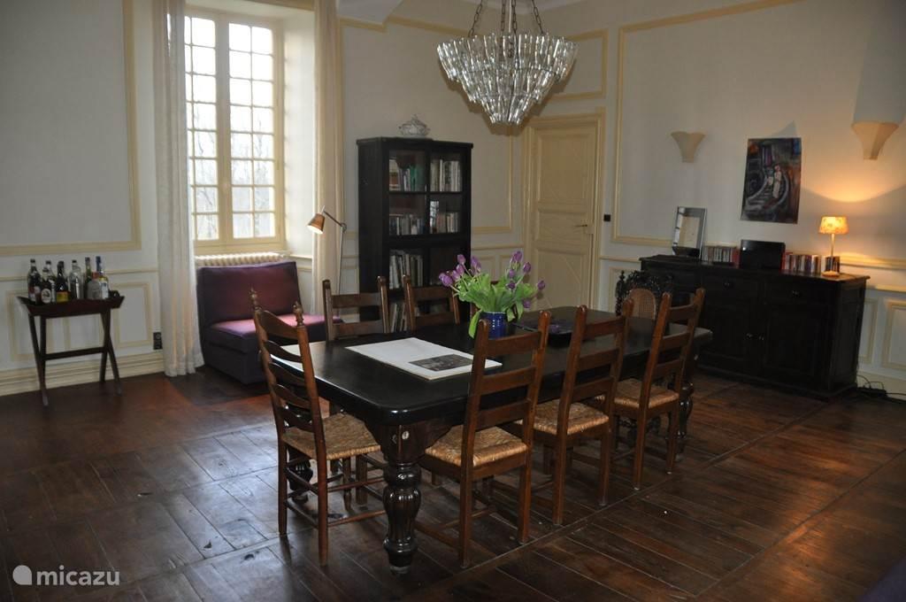 De eetkamer met een grote tafel voor 8 personen en 2 heel makkelijke stoelen om je even terug te trekken met een boek. Er is een piano en cd-speler met collectie cd's. Ook hier de originele, authentieke houten vloer.