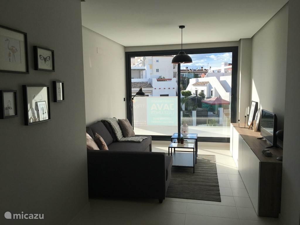 WOONKAMER Het appartement heeft een ruime, modern ingerichte woonkamer voorzien van alle comfort. Van hieruit heeft u via een groot schuifraam toegang tot het privé terras.