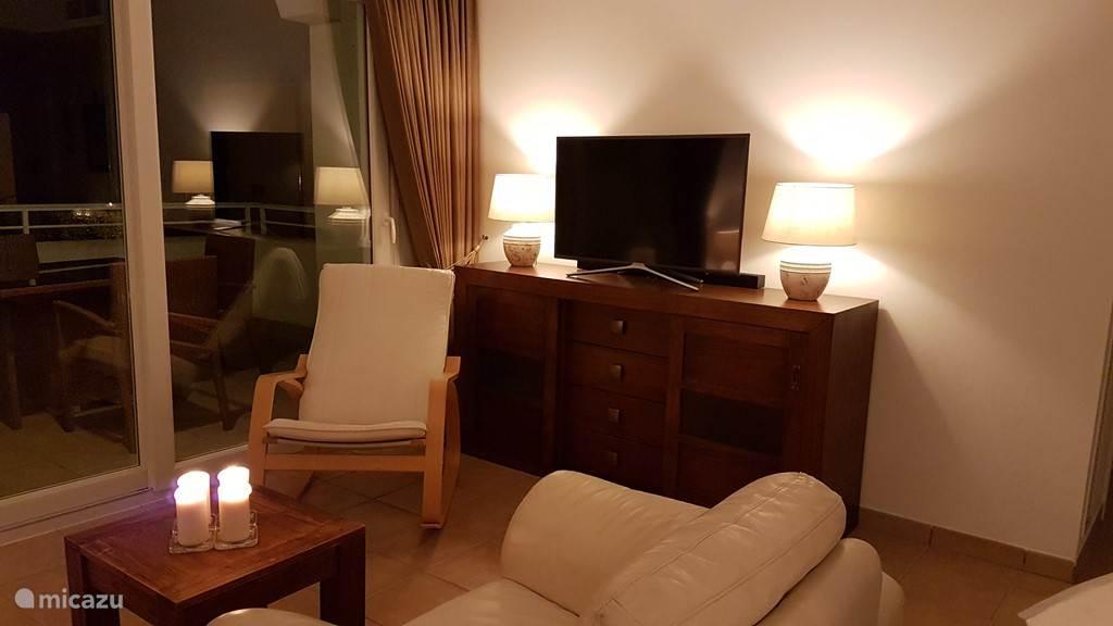 Gezellige woonkamer met 40 TV, Canal Digitaal (Nederlandse zenders), soundbar en schemerlampen op afstandsbediening.