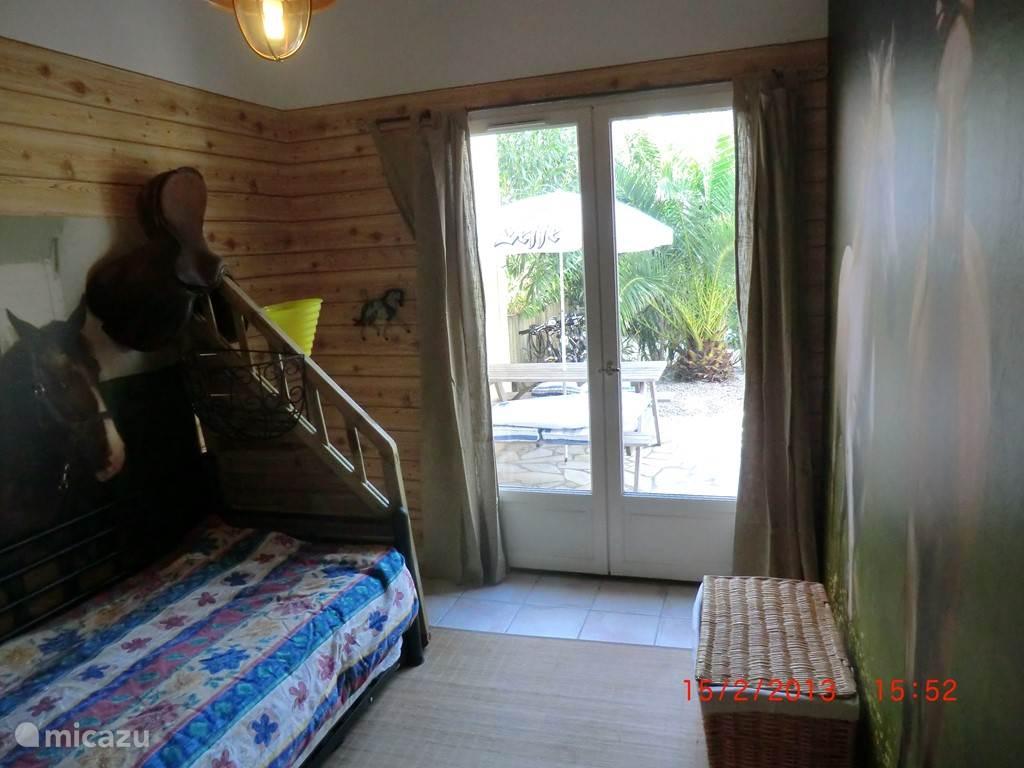 Slaapkamer beggr met 2 x 1 persbedden, deur naar terras.