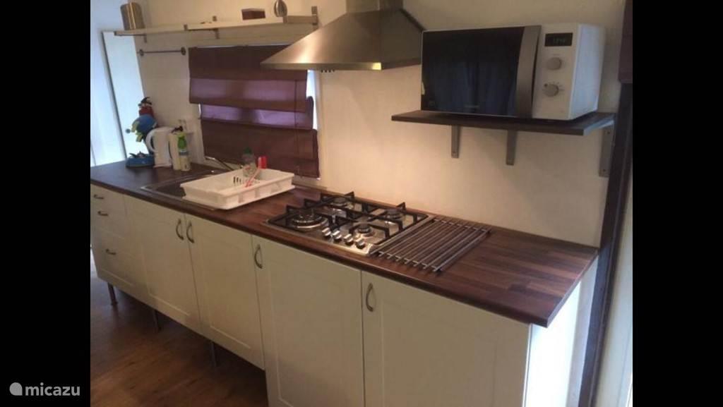 Keuken met koelkast, gasfornuis en magnetron