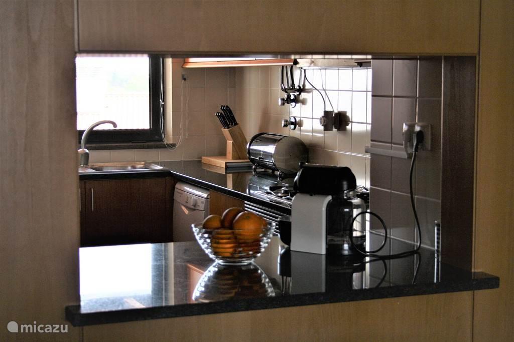 Een ruime keuken met alle apparatuur zoals onder meer een vaatwasmachine en een wasmachine.