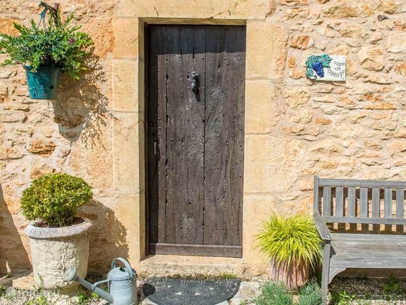 De hoofdingang van Vigne de Montagne, een markante oude houten deur.