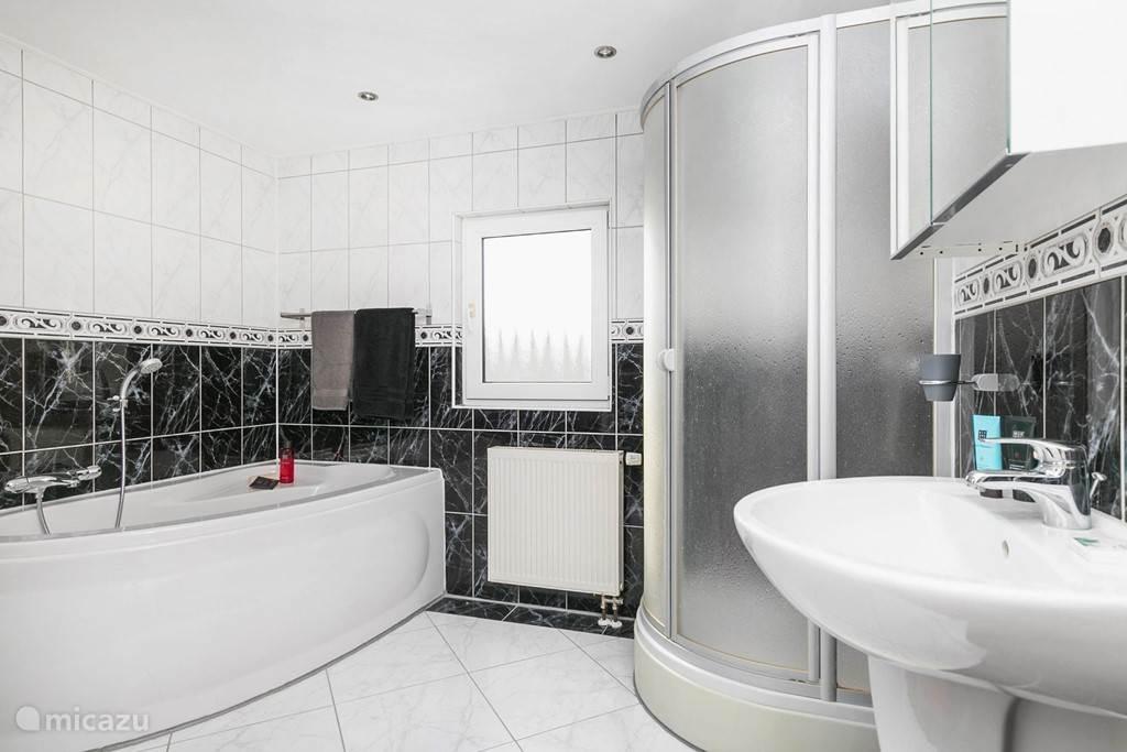 Badkamer met ligbad, douche en toilet